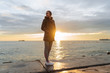 a young girl in a warm jacket walks along the sea promenade at sunset, listening to music on headphones