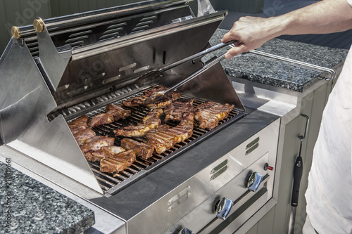 Canvastavla modern outdoor propane gas grill with man turning stakes
