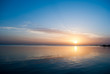 Orange sunrise in blue sky above ocean. Early Morning blue sky with clouds and sun above sea. Sunrise on blue sky and cold water. Water reflex