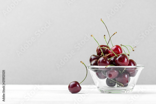 Fototapeta Red sweet cherries in a glass bowl on a white wooden table close-up