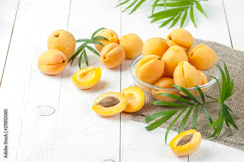 Fresh apricots in a round glass pial on a white board close-up..