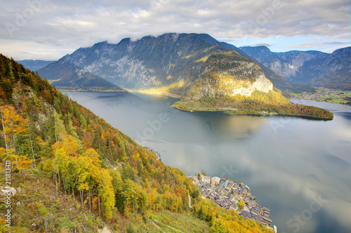 Foto op Canvas Bergen Aerial view of Hallstatt village by the lake and colorful fall mountains lighted up by beams of sunlight on a brisk autumn day, an amazing lakeside village in Salzkammergut region of Austria