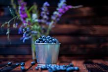 Blueberries In A Bucket On A Dark Wooden Background .field Flowers. Rustic Style