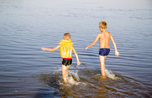 Two Teenagers Of Different Age Go Swimming In The River
