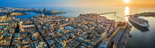 Valletta, Malta - Aerial Panoramic View Of Valletta With Mount Carmel Church, St.Paul's And St.John's Cathedral, Manoel Island, Fort Manoel, Sliema And Cruise Ship Entering Grand Harbor At Sunrise