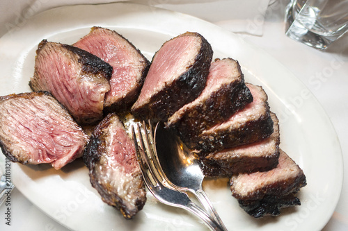 Fotografie, Obraz  seared medium rare stake cut on white plate with spoon and fork