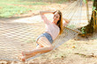 Young blonde girl lying in white wicker hammock on sand, wearing jeans shorts and shirt. Concept of summer vacations and resting on beach.