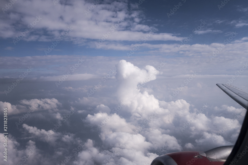 Looking Out The Window Of An Airplane Above The Cumulonimbus Clouds