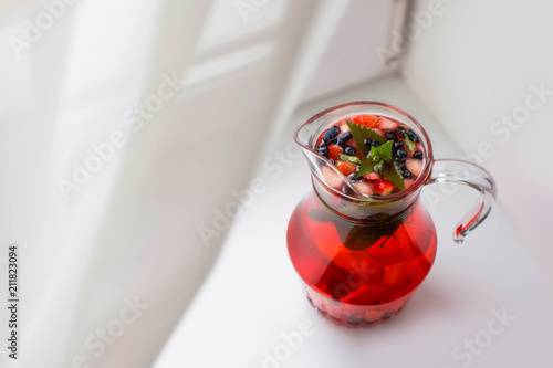 Pitcher filled with cooling drink of berries with lemon and mint leaves on the windowsill