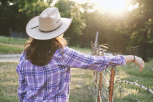Western Rural Farm Scene With Cowgirl In Cowboy Hat And Plaid Shirt Overlooking Pasture During Sunset.  Strong Woman In Country Lifestyle.