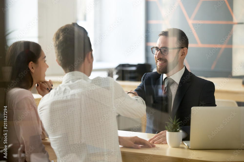 Fototapeta Smiling male realtor or broker shaking hand of excited buyers couple, negotiating about first house purchase or taking loan, insurance agent welcoming clients with handshake at consultation meeting