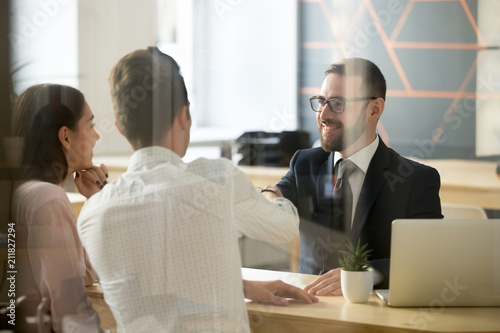 Stampa su Tela  Smiling male realtor or broker shaking hand of excited buyers couple, negotiatin