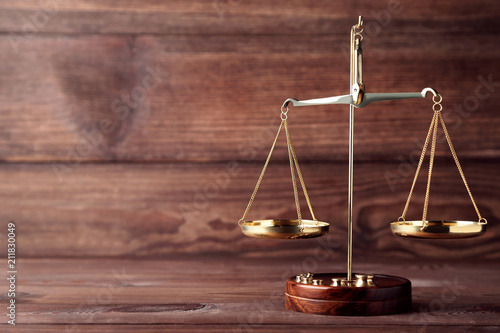 Scales of justice on brown wooden table