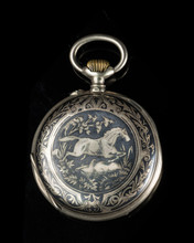 Old Pocket Watch On A Black Reflective Surface, Closed Lid With Horse Motive