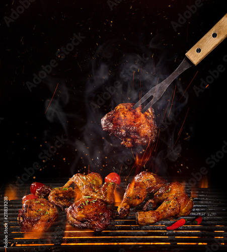 Fototapeta Chicken legs and wings on the grill with flames obraz