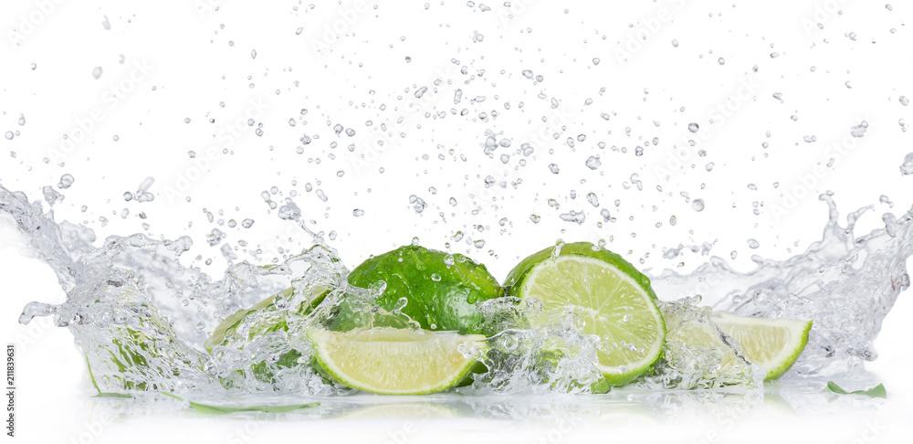 Fototapeta Fresh limes with water splash over white background.
