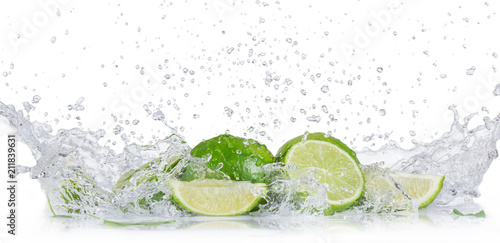 Fresh limes with water splash over white background.