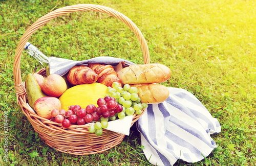 Spoed Foto op Canvas Picknick Basket with Food Fruit Bakery Cheese Ham Tomato Picnic Green Grass Summer Time Rest Background Toned Photo