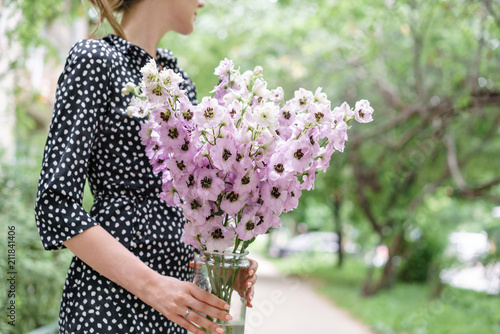 Foto Young girl holding a flower bouquet with Delphiniums of lilac color in glass vase
