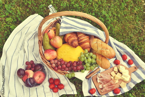 Poster Picknick Basket with Food Fruit Bakery Cheese Ham Tomato Picnic Green Grass Summer Time Rest Background Toned Photo