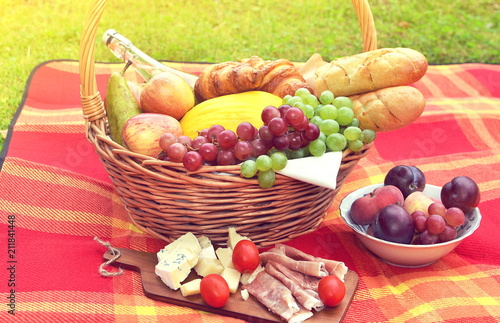 Keuken foto achterwand Picknick Basket with Food Fruit Bakery Cheese Ham Tomato Picnic Green Grass Summer Time Rest Background Toned Photo