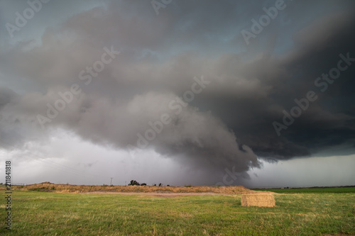 A supercell storm with a low shelf cloud hangs ominously over farmland in Nebraska.
