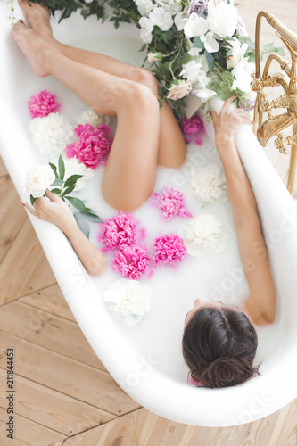 Fotografie, Obraz  Young beautiful woman taking bath with flowers and milk
