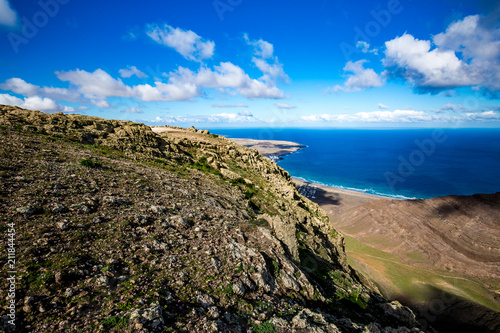 Tuinposter Canarische Eilanden Lanzarote, Canary Islands, Spain, elevated landscape view from mountain peak of blue Atlantic Ocean with expressive bright spring sky with white clouds