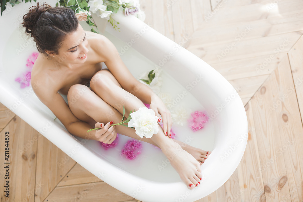 Fototapeta Young beautiful woman taking bath with flowers and milk