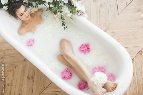 Vászonkép Young beautiful woman taking bath with flowers and milk