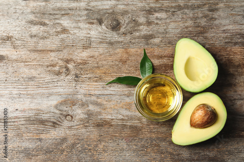 Fotografia Gravy boat with oil and ripe fresh avocado on wooden table, top view