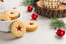 Traditional Christmas Linzer Cookies With Sweet Jam And Bowl On Table