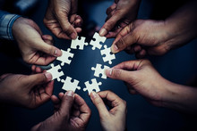 Hands Of Business People Wearing Casual Plaid Shirt Hold Paper Jigsaw Puzzle And Solving Puzzle Together,Business Team Assembling Jigsaw Puzzle,Business Group Wanting To Put Pieces Of Puzzle Together.