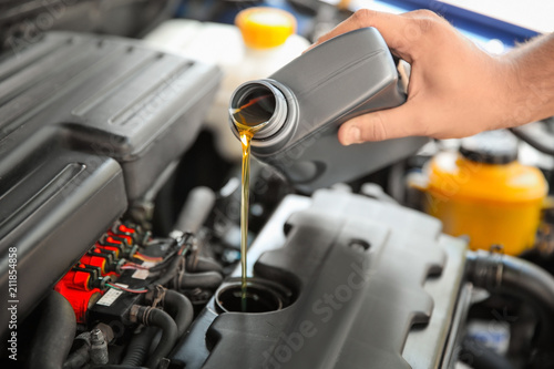 Fotomural Mechanic pouring oil into car engine, closeup