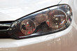 Left headlight of the new clean white sports car