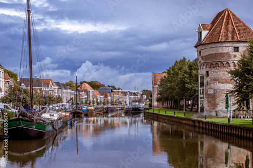 Canal view in a Dutch city with an old defence wall and tower just after rainfall