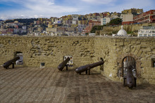 Ovo Castle Fortifications With Canons At Castel Dell Ovo Islet Fortress And City View At The Gulf Of Napoli, Naples, Campania