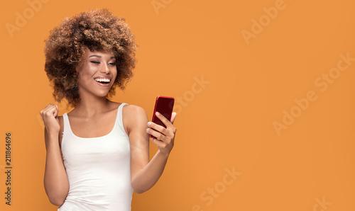Fototapeta Cheerful afro woman using smart phone. obraz
