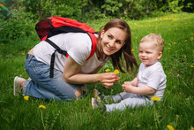 Family. Son And Mother Outdoors. Pregnant Girl With Backpack Is Sitting On Lawn And Holding Yellow Dandelion In Her Hands. Little Boy And Mother Are Looking Aside