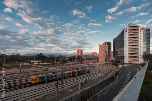 Photo Train leaves the city of Adelaide as the sun sets