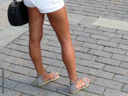 f9132eea7777 Slim girl in a white mini shorts with tanned legs standing on the sidewalk.  Summer female fashion