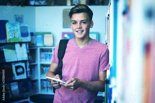 Photo  Portrait of happy schoolboy holding digital tablet in library