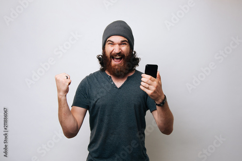 Fotografiet  Cheerful young bearded man wearing grey T-shirt and fur cap hat is surprised and happy