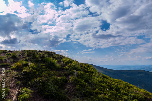 Foto op Canvas Blauwe jeans blue sky with fluffy white clouds touching the top of a high mountain