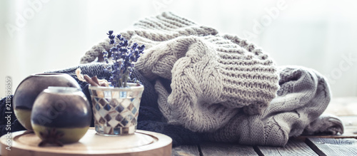 Knitted sweaters on a wooden background in the interior