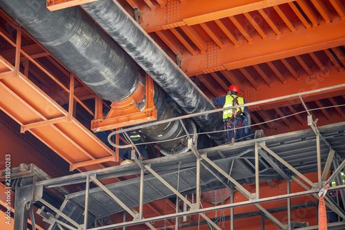 Workers welding work on district heating pipes under metal bridge Fototapet