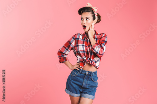 Portrait of a shocked beautiful brunette pin-up woman
