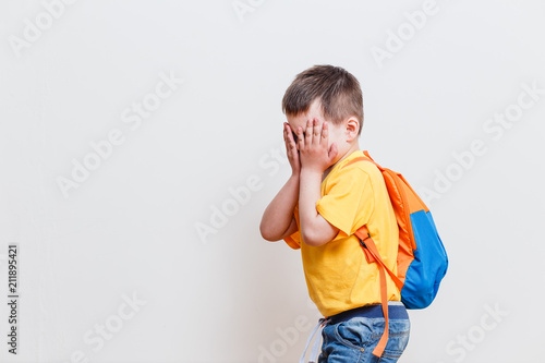 Fotografie, Obraz  boy covers his face with his hands on a white background