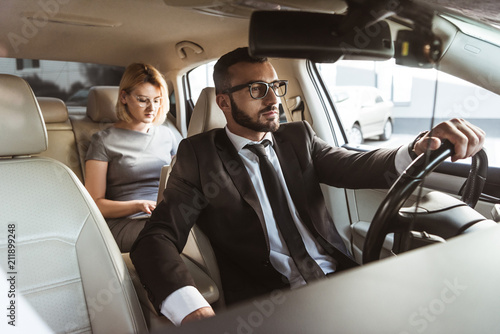Obraz handsome driver and attractive businesswoman in car - fototapety do salonu
