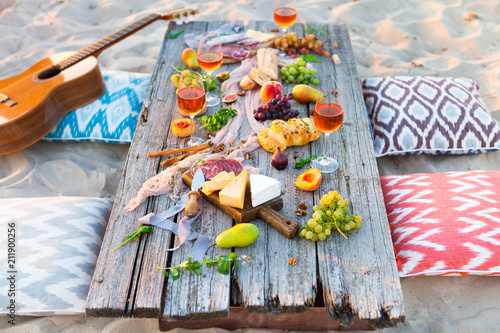 Keuken foto achterwand Picnic on beach at sunset in boho style. Romantic dinner, friends party, summertime, food and drink concept